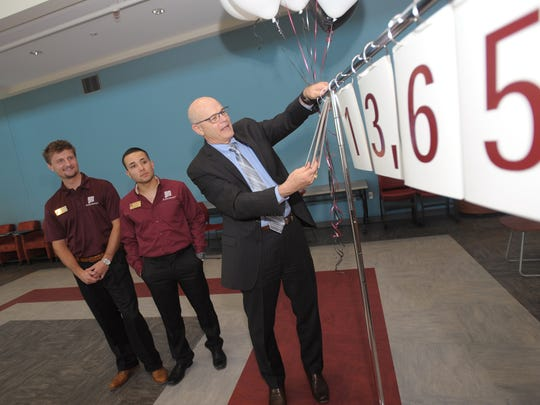 NMSU provost Dan Howard, right, helps out during the