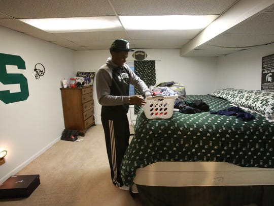 Brandon Randle, 18, packs clothes to travel to Raleigh, North Carolina, for Christmas with his family, on Tuesday, Dec. 22, 2015. Randle goes to school at Battle Creek Central High School and lives with his football coach, Lorin Granger, and his family. Randle was going to return to Raleigh after his grandfather, who he was living with in Battle Creek, was in a car accident his junior year.