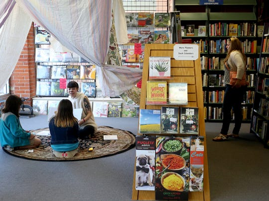 C.J. Jensen, an employee of the Book Bin, reads a story to sisters Paisley, left, 9, and India Elias, 10, of Salem, as Ashley Sanblise, 31, of Salem, browses the shelves at the shop in downtown Salem on Saturday, April 30, 2016. The Book Bin held special events and gave away prizes as part of the national celebration of Independent Bookstore Day. Jensen dressed as a lamb as part of a group costume with Little Bo Peep and her sheep.