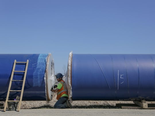 Zito Construction worker Brian Townsend preps a 50ft. section of pipe for welding that is part of the companies 13-mile section of Karegnondi Water Authority pipeline on Klam Rd. in Columbiaville on Friday April 15, 2016.