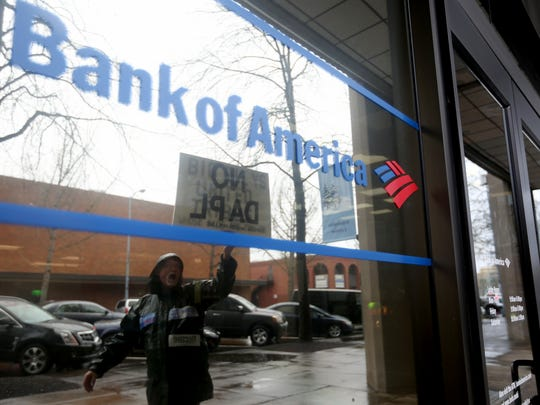 Gregory Gregg, 70, of West Salem, is reflected in the windows of Bank of America during a protest and march in downtown Salem urging four nationwide banks to defund the Dakota Access Pipeline on Saturday, Feb. 4, 2017. The protesters rallied outside the downtown Salem branches of Wells Fargo, U.S. Bank, Bank of America and Chase banks.