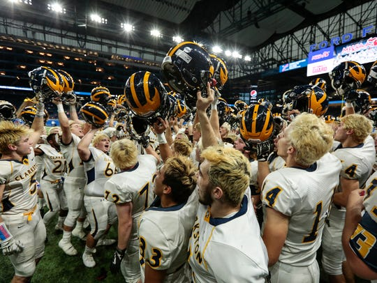 Clarkston players and coaches celebrate winning the