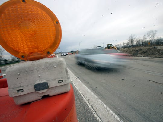 Motorists drive through a gauntlet of orange construction barrels on eastbound M14 near Sheldon road.