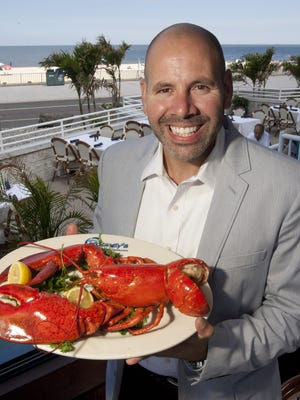 Darrell Wordelmann, general manager at Rooney's Oceanfront Restaurant in Long Branch, holds a large lobster, ready to eat.