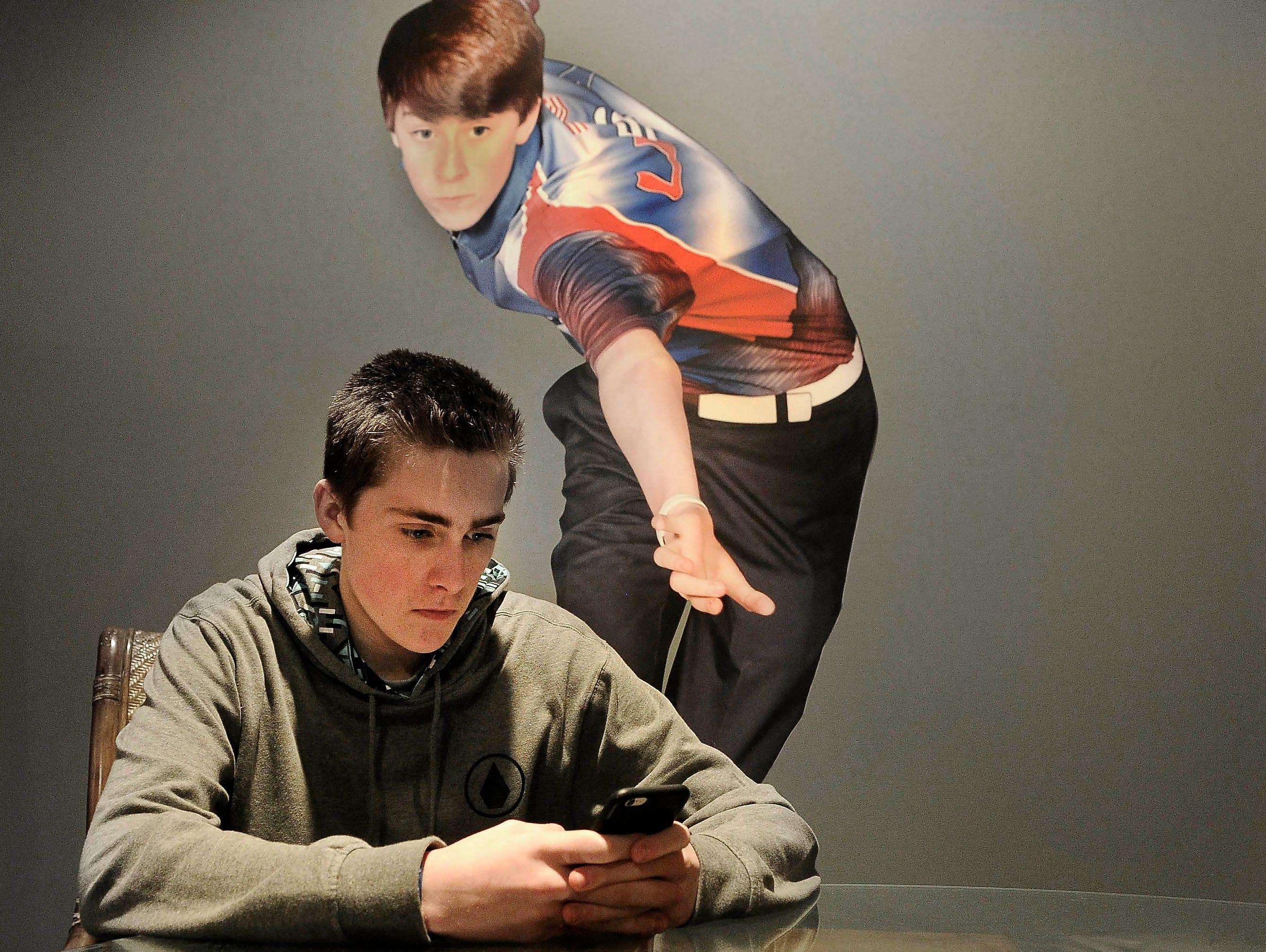 Kamron Doyle checks messages at his home.