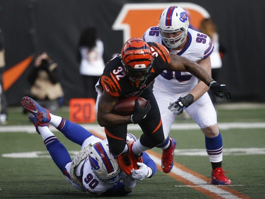 Buffalo Bills defensive end Shaq Lawson (90) tackles Cincinnati Bengals running back Jeremy Hill (32) in the first half Sunday in Cincinnati.