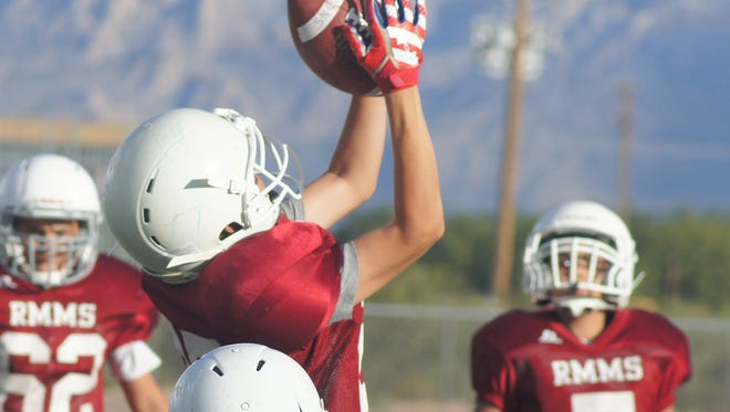 Adrian Lopez leaps high in the air to intercept a Snell Junior High pass during Red Mountain Middle School's seventh-grade football win over the visiting Redskins. Lopez and the Wildcats celebrated a 28-6 victory where the Cats outscored their opponents 20-0 in the second half.