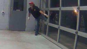 Surveillance image shows a man entering Burlington City car dealership through a broken window.