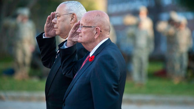 Former Secretary of State and retired Gen. Colin Powell, left, and Gordon Sullivan, retired general and former Army chief of staff, salute after laying a wreath during Veterans Day observances at Norwich University in Northfield on Tuesday.