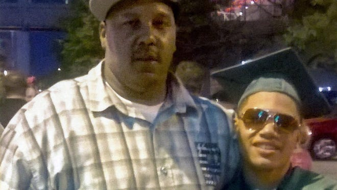Terrill Thomas poses with his 20-year-old son, also named Terrill, at his son's high school graduation in 2014.