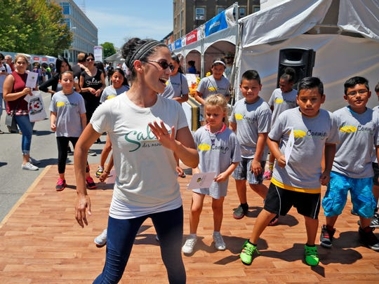 Melanie Gella of salsa Des Moines leads kids in a dance during the Des Moines Arts Festival Friday, June 24, 2016.