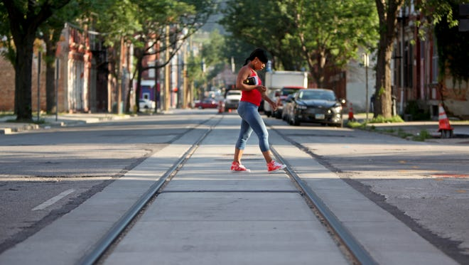 A young woman crosses the completed streetcar tracks along Race Street in Over-the-Rhine.