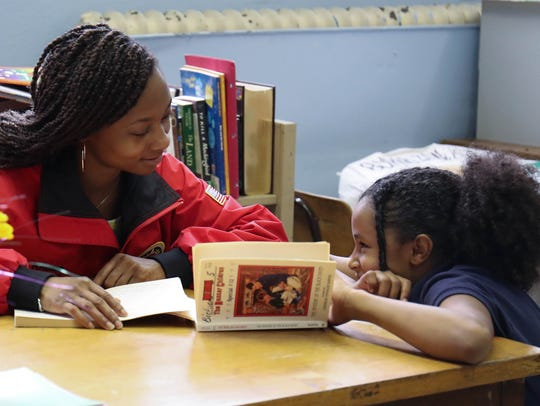 City Year mentor Kristian Rice works on reading with
