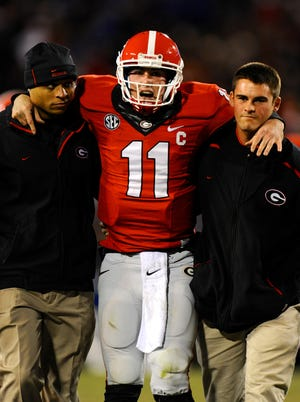Georgia Bulldogs quarterback Aaron Murray (11) leaves the field injured against the Kentucky Wildcats during the second quarter at Sanford Stadium.