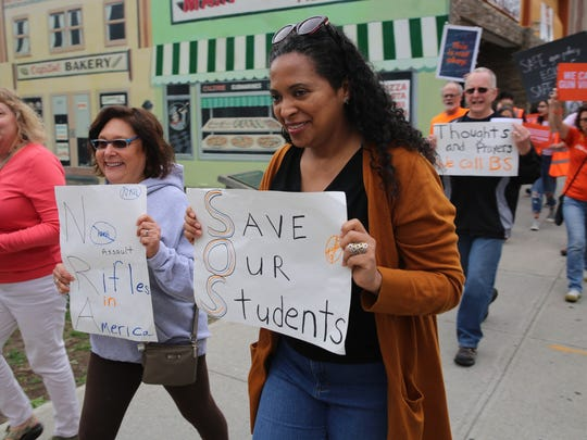 """Monica Angulo, 44, of Hyde Park, marches through the City of Poughkeepsie on Sunday. She said """"this is the only country where we have this big problem."""""""