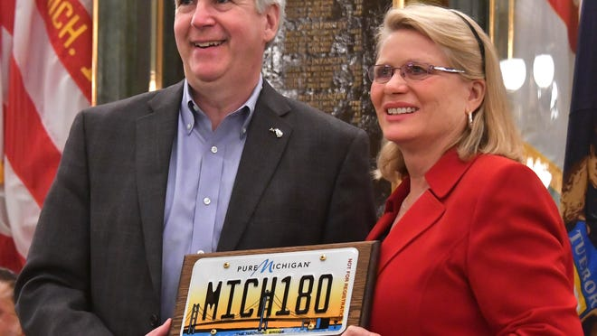 Michigan Governor Rick Snyder and Secretary of State Ruth Johnson take a moment to pose with a ceremonial plate and plaque as a host of Michigan dignitaries speak during a ceremony marking the 180th birthday of the State of Michigan in the Capitol Rotunda in Lansing.