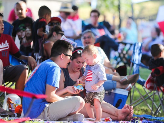 Attendees sit on blankets and lawn chairs during the