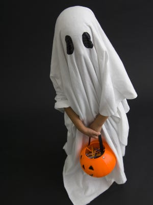 Child in ghost costume trick or treating.
