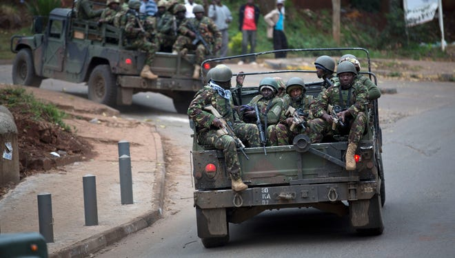 Trucks of soldiers from the Kenya Defense Forces arrive after dawn outside the Westgate Mall in Nairobi.