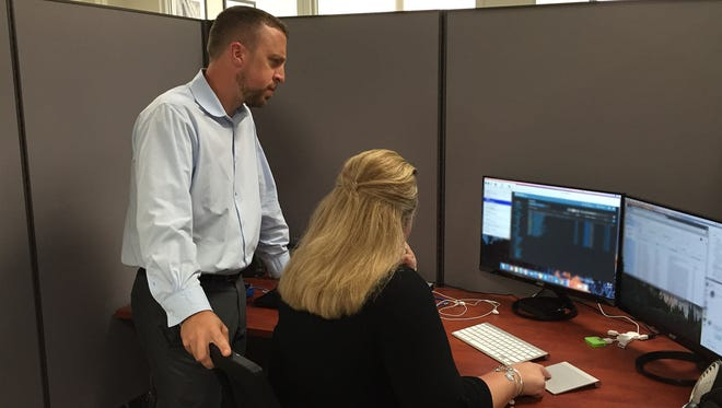 Aaron White and Tara Williams, managing partners of the Flemington-based IT firm eSOZO, review data backup settings for a customer. The firm was hailed as partner for the Cloud Era in Enterprise Services Outlook Magazine's recent issue on disaster recovery.