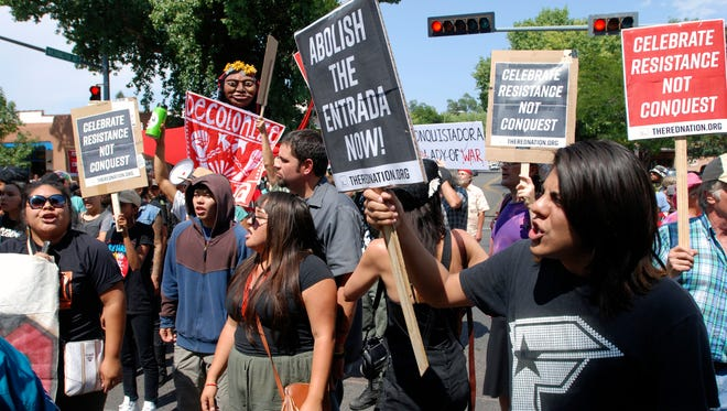 """Protesters in Santa Fe chant slogans on Friday, Sept. 8, 2017, against an annual costumed re-enactment of the arrival or """"entrada"""" of Spanish conquistador Don Diego de Vargas in 1692 after an Indian revolt drove out Spanish settlers. Santa Fe police say they arrested at least 12 people at the protests. Public statues and tributes to early Spanish conquerors are facing mounting criticism tied to the brutal treatment of American Indians centuries ago by Spanish soldiers and missionaries, with activists drawing ethical parallels to the national controversy over Confederate monuments."""