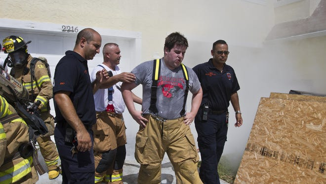 After participating in a series of hands-on fire training exercises, reporter Frank Bumb is checked by emergency personnel to check his condition after working in extreme hot conditions Tuesday morning in Cape Coral.