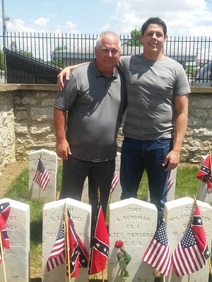 In this May 30, 2016 photo, Gregory Beckman and his son, Marcus, visit the grave site of their relative Augustus Beckmann at Camp Chase Confederate Cemetery on Memorial Day weekend. The name and information on the stone is incorrect. Due to Beckman's efforts in tracking down his family history and noting that the stone is wrong, a national cemetery association will fix it.