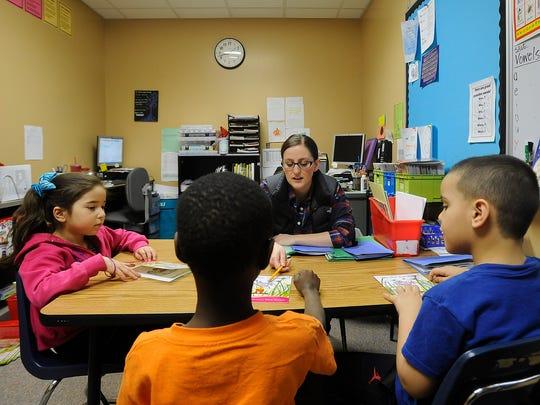 Kelsey Ellens, LIA Teacher, reads with Estrella Castaneda, Gamr Dokman and Tariku Tamire at Terry Redlin Elementary in Sioux Falls, S.D., Monday, Feb. 22, 2016.