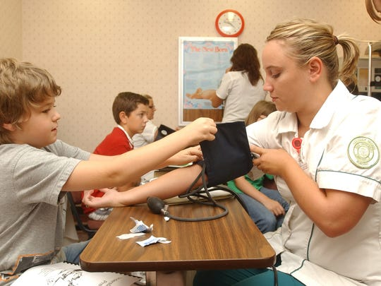 Joseph Swingle, a fourth-grader at Crooksville Elementary School, and Ohio University-Zanesville nursing student Lea Bush take Bush's blood pressure during OUZ's So You Want to be a Nurse program. The program is aimed at raising awareness of the profession among younger students and featured hands on demonstrations of basic nursing skills and presentations on various subjects.