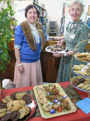 Sara Cote (left) and Claire Pryor serve up a batch of Christmas cooies.