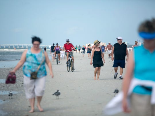 Snowbirds and vacationers make their way north on Fort Myers Beach on Thursday.