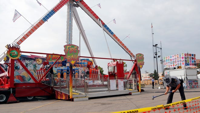 "An Ohio State Highway Patrol trooper removes a ground spike in front of the fire ball ride July 27 at the Ohio State Fair in Columbus, Ohio. The Dutch manufacturer of the thrill ride, which broke apart and killed an 18-year-old man, says excessive corrosion on a support beam led to a ""catastrophic failure."" A statement on KMG's website dated Friday, Aug. 4, says the company officials visited the accident site and conducted metallurgical tests."