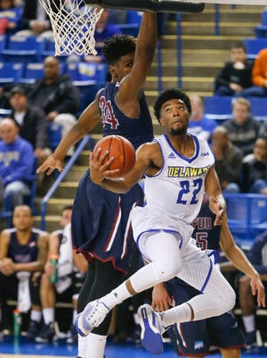Delaware's Cazmon Hayes goes around Fairleigh Dickinson's Mike Holloway for two points in the first half at the Bob Carpenter Center Tuesday.