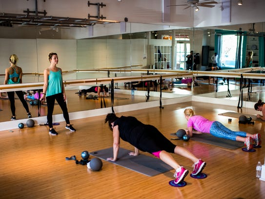 Exercisers participate in a class at Xtend Barre in