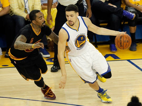 Klay Thompson handles the ball against J.R. Smith during