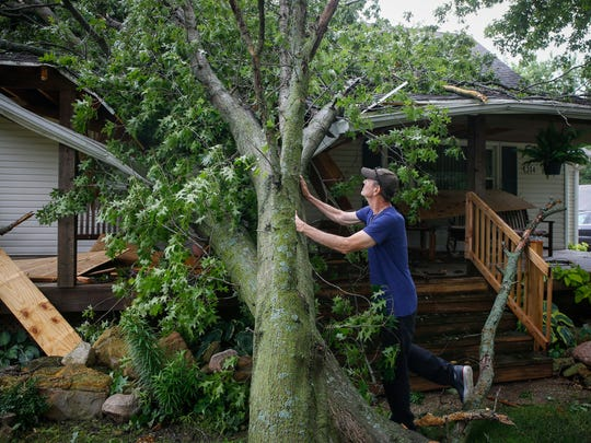 Ron Routh observes damage to his home in Norwalk after a large tree limb fell on his front porch during a strong afternoon storm on Thursday, June 28, 2018.