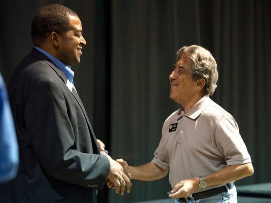 State Sen. John Kefalas, right, receives a medallion