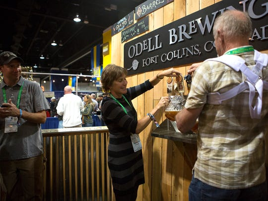Owner Wynne Odell of Odell Brewing pours beer at the Great American Beer Festival at the Colorado Convention Center in Denver Friday, Oct. 3, 2014.