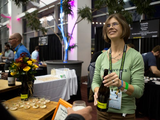 Carolee Schuck of Funkwerks pours beer at the Farm to Table event at the Great American Beer Festival at the Colorado Convention Center in Denver Friday, Oct. 3, 2014.