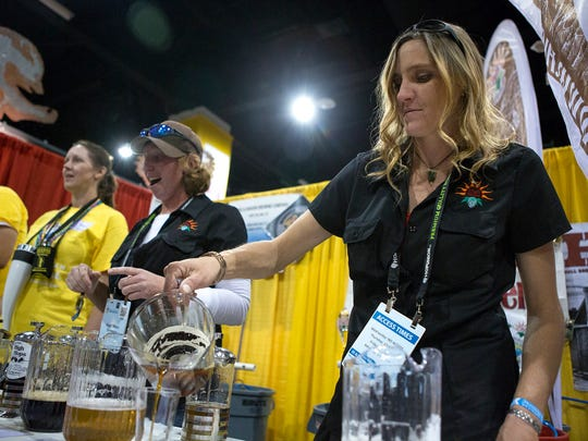 Melinda Parker of High Hops Brewery and garden center in Windsor pours peer at the Great American Beer Festival at the Colorado Convention Center in Denver Friday, Oct. 3, 2014.