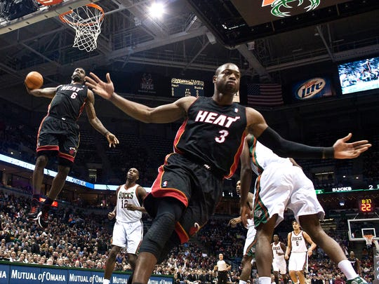 Miami Heat's Dwyane Wade reacts as teammate LeBron James goes up for a dunk during the first half of a game against the Milwaukee Bucks.