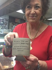 "Rosemarie Papa shows a koozie drink holder that will soon be sold at Papa's Food Market in Wilmington. It has the late Ralph Papa's famous saying, ""It's just a 'little' over."""