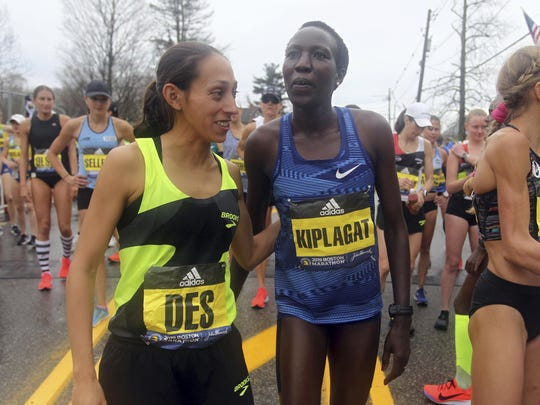 Des Linden, left, last year's Boston Marathon winner from Washington Township, embraces Edna Kiplagat, right, of Kenya, prior to the start the Boston Marathon on Monday in Hopkinton, Mass.