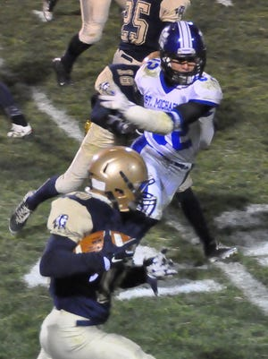 Ruidoso's Hayden Frierson stops Saint Michael's Miguel Montoya as Cisco Mayville makes gains for the Warriors.