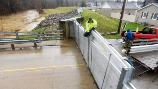 Workers reach to place a piece of the flood gate in Rosesville on Tuesday.