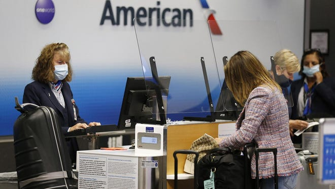 An American Airlines agent tends to customers in Terminal C at Dallas-Fort Worth International Airport on July 21, 2020.