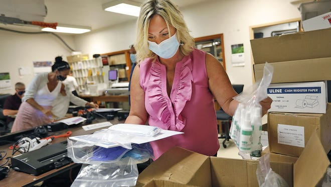 Quincy City Clerk Nicole Crispo sorts through boxes of sanitizing products and protective equipment for each polling place in the city on Tuesday August 18, 2020. Greg Derr/The Patriot Ledger