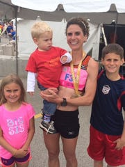 "Flanked by daughter Evelyn, 6, on left, and oldest son Ryne, 10, Erin Moeller of Mount Vernon, Iowa, holds youngest son Kellyn, 21 months, after winning the women's title in the Cellcom Green Bay Marathon for the second time Sunday. Kellyn is wearing the same ""My Mommy Rocks!"" T-shirt worn by Ryne when Erin won her first Green Bay Marathon title in 2007."