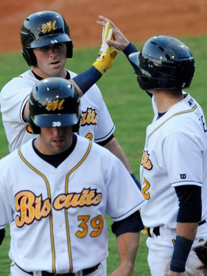 Montgomery Biscuits' Willie Argo, back, is welcomed to the dugout after hitting a two run home run in the first against the Mississippi Braves at Riverwalk Stadium in Montgomery, Ala. on Monday July 7, 2014.