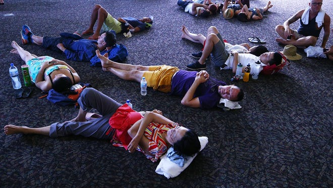 Tennis fans escape the heat by resting on the concourse floor of Hisense Arena during day four of the 2014 Australian Open at Melbourne Park on January 16, 2014 in Melbourne, Australia.  Heat waves in Australia in 2014 were worsened by climate change, a new study says.